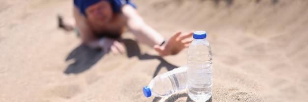 Homem esticando as mãos com uma garrafa plástica de água no deserto.