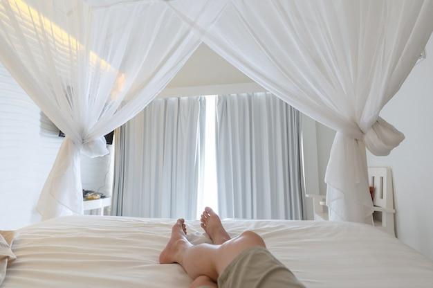 Homem esticando as pernas com mosquiteiro na cama nas férias, luz do sol através da cortina branca no quarto