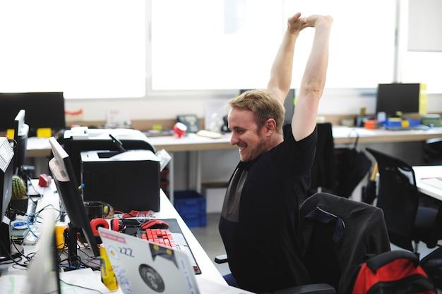 Homem, esticando os braços durante o tempo de pausa no escritório
