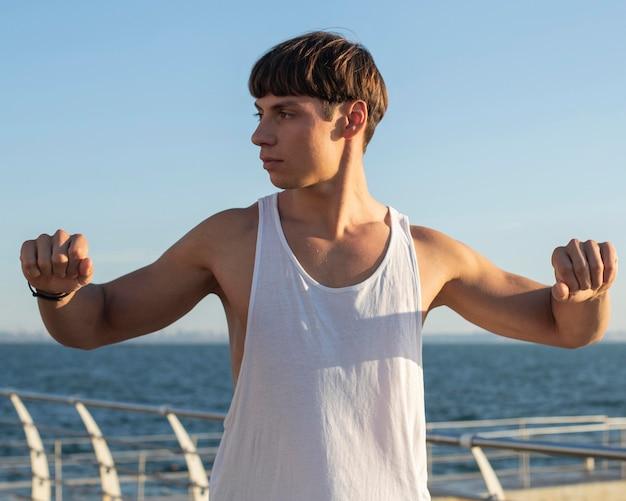 Homem esticando os braços na praia