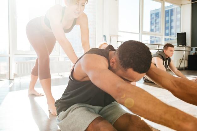 Homem, esticar e malhar com o treinador no estúdio de yoga