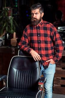 Homem estiloso barbudo. homem estiloso na barbearia. barbearia na moda. homem estiloso com barba na camisa xadrez em pé perto da cadeira de barbeiro vintage.