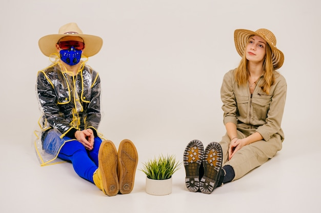 Homem estiloso com a máscara e mulher com chapéu de palha posando com grama na panela sobre fundo branco