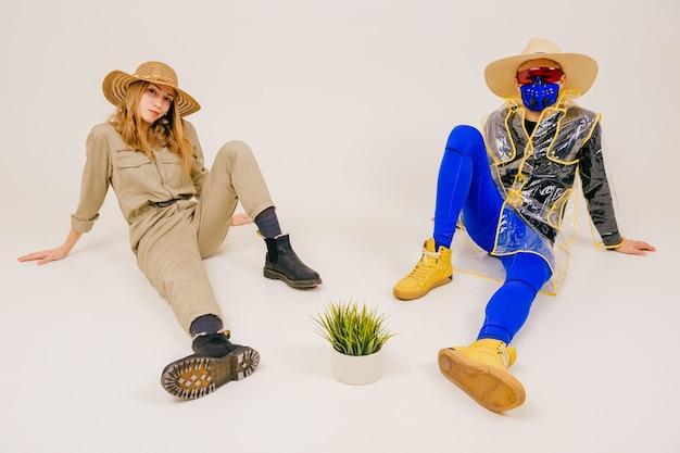 Homem estiloso com a máscara e mulher com chapéu de palha posando com grama na panela sobre uma parede branca