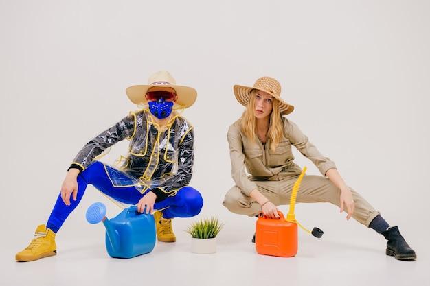 Homem estiloso com a máscara e mulher com chapéu de palha posando com um regador na parede branca
