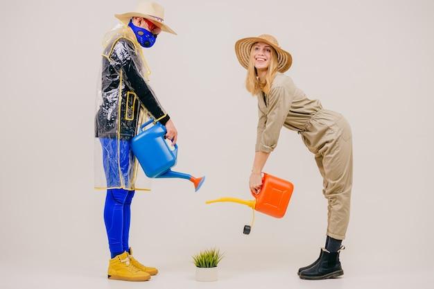 Homem estiloso com a máscara e mulher com chapéu de palha regando a grama na panela sobre a parede branca