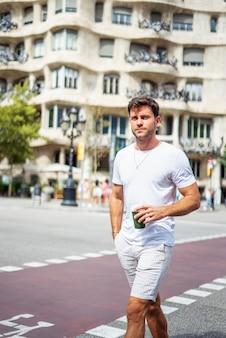 Homem estiloso com café para viagem na cidade