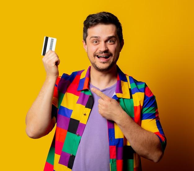 Homem estiloso com camisa dos anos 90 e cartão de crédito