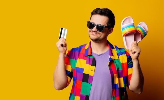 Homem estiloso com camisa dos anos 90, sapatos e cartão de crédito