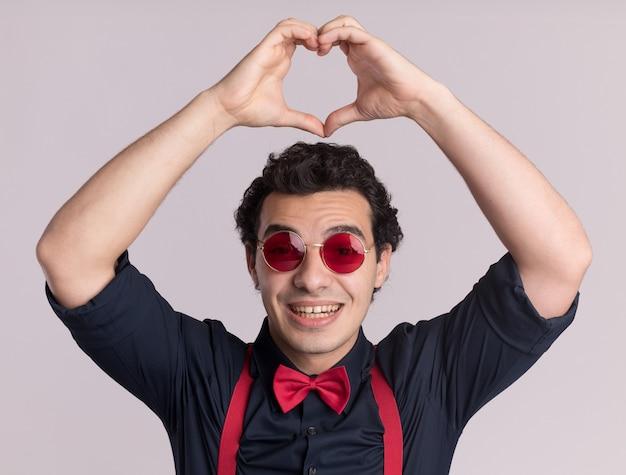 Homem estiloso com gravata borboleta usando óculos e suspensórios, fazendo um gesto de coração com os dedos na cabeça, sorrindo com uma carinha feliz em pé sobre uma parede branca