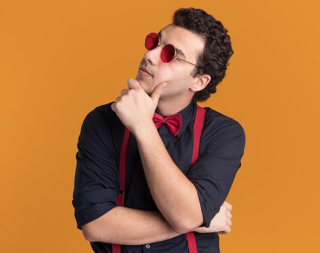 Homem estiloso com gravata borboleta usando óculos e suspensórios olhando para o lado com a mão no queixo pensando em pé sobre uma parede laranja