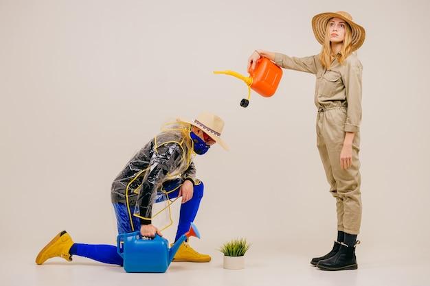 Homem estiloso com máscara e mulher com chapéu de palha posando com um regador na parede branca