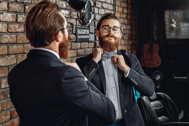 Homem estiloso com óculos, barba e bigode, olhando-se no espelho e endireitando uma gravata borboleta no colarinho.