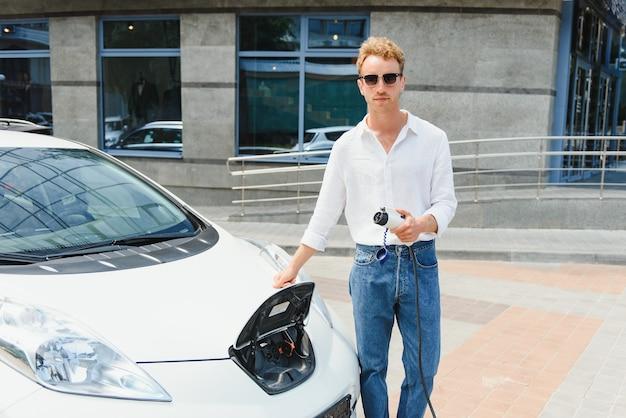 Homem estiloso com uma xícara de café na mão e conecta o plugue à tomada de carga do carro elétrico