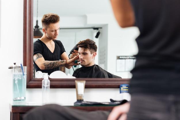 Homem estiloso cortado por um barbeiro profissional com tesoura