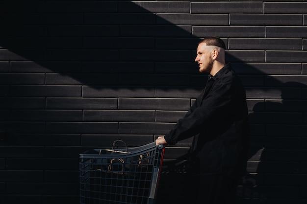 Homem estiloso de preto com sacolas de compras em um carrinho na sexta-feira negra