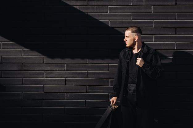 Homem estiloso de preto com sacos de compras na sexta-feira negra