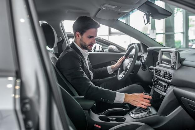 Homem estiloso de terno no showroom de carros