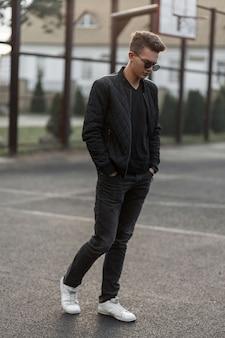 Homem estiloso e moderno em roupas pretas da moda com sapatos brancos posa em estádio ao ar livre