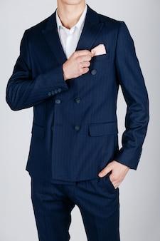 Homem estiloso em um casaco azul sobre um fundo claro