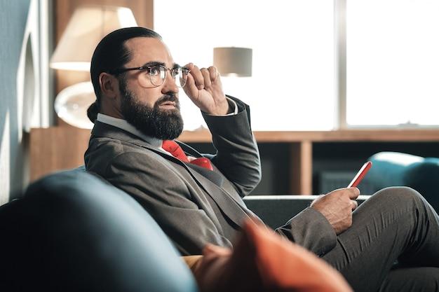 Homem estiloso. empresário barbudo e elegante, de cabelos escuros, vestindo um belo traje de negócios e gravata vermelha