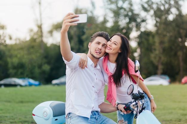 Homem estiloso na scooter fazendo caretas engraçadas enquanto tira fotos com uma mulher elegante de cabelos escuros