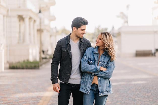 Homem estiloso, olhando para a namorada com amor. retrato ao ar livre da menina encaracolada se divertindo no encontro.