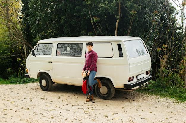 Homem estiloso posando perto de van branca com mochila de exploração