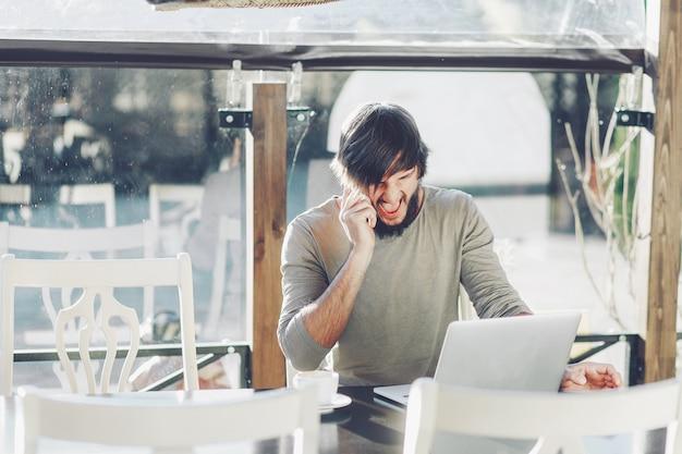 Homem estiloso sentado no café com laptop