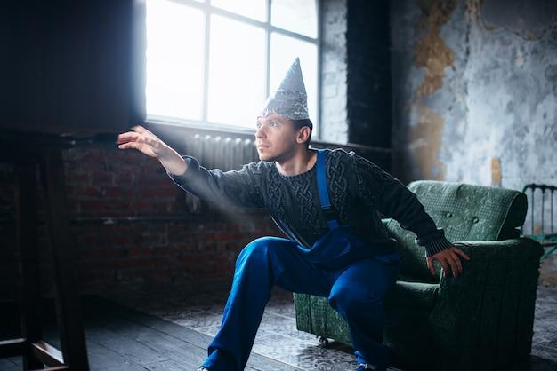 Homem estranho com chapéu de papel alumínio estende a mão para a tv, ovni