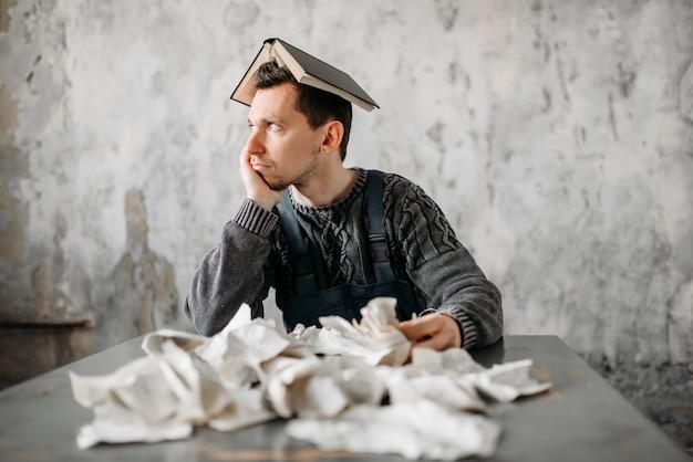 Homem estranho com um livro na cabeça contra uma pilha de lençóis rasgados.