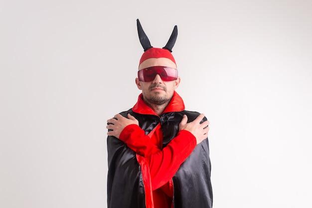 Homem estranho e diabólico com óculos escuros e fantasia de halloween preto e vermelho posando