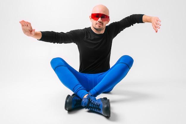 Homem estranho em roupas elegantes e óculos de sol vermelhos, posando no estúdio branco