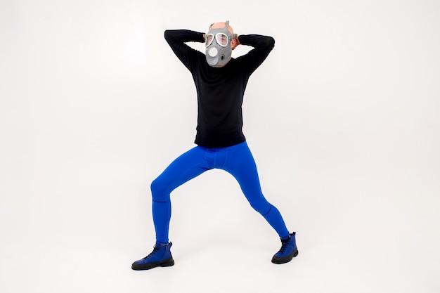 Homem estranho engraçado com respirador posando sobre uma parede branca