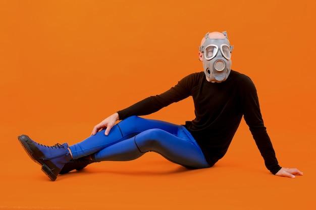 Homem estranho engraçado com respirador posando sobre uma parede laranja