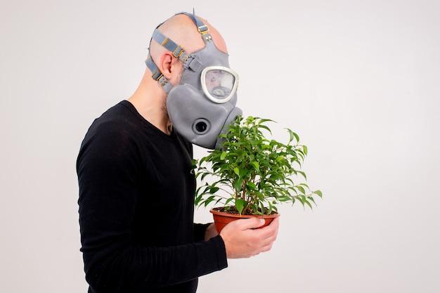 Homem estranho engraçado no respirador cheirando uma flor no vaso sobre fundo branco
