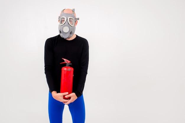 Homem estranho engraçado no respirador com extintor de incêndio posando sobre fundo branco