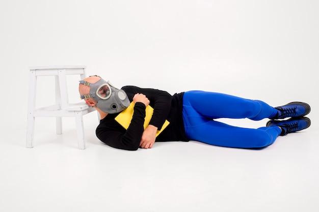 Homem estranho engraçado no respirador deitado com livro sobre fundo branco