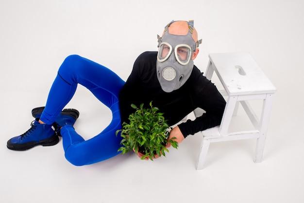 Homem estranho engraçado no respirador deitado com uma flor na panela sobre fundo branco