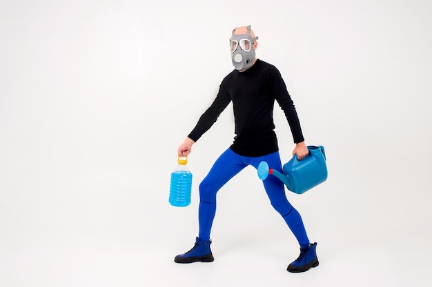 Homem estranho engraçado no respirador posando com regador e garrafa sobre fundo branco