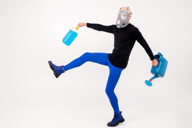 Homem estranho engraçado no respirador posando com um regador e uma garrafa na parede branca