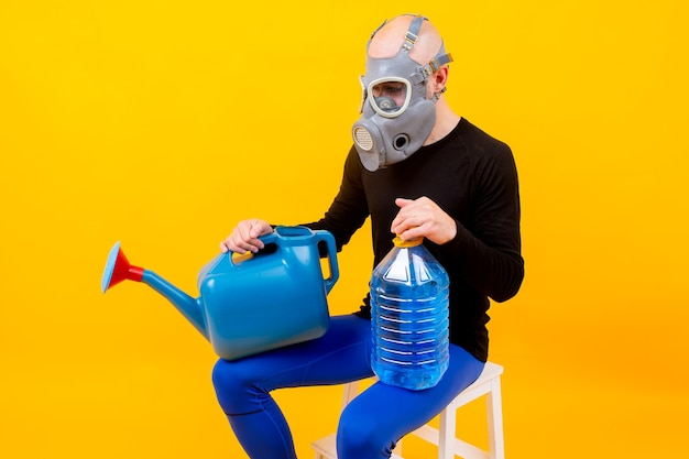Homem estranho engraçado no respirador sentado na escada com regador sobre fundo amarelo