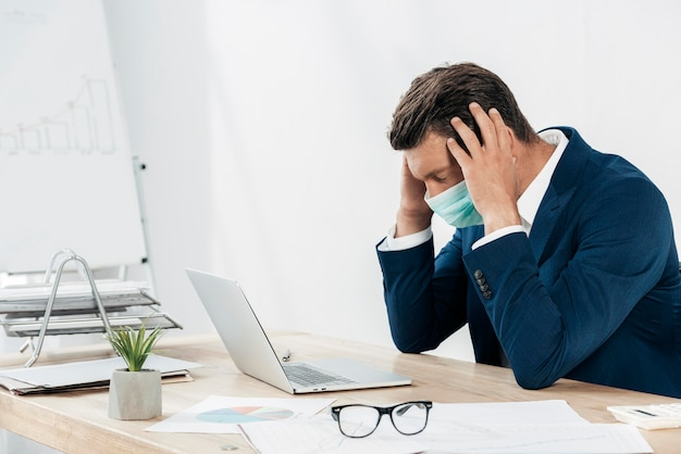 Homem estressado com tiro médio e laptop