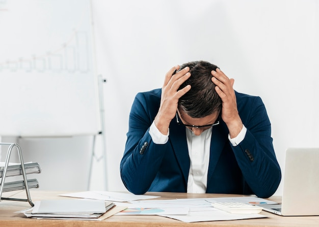 Homem estressado em tiro médio olhando para papéis