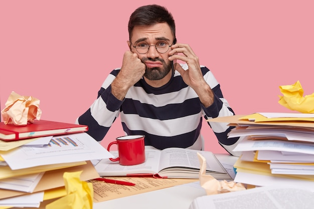 Homem estressante e descontente tem a barba por fazer, conversa ao telefone, sente-se cansado de trabalhar muito tempo, vestido com um macacão listrado, senta-se na mesa com papéis