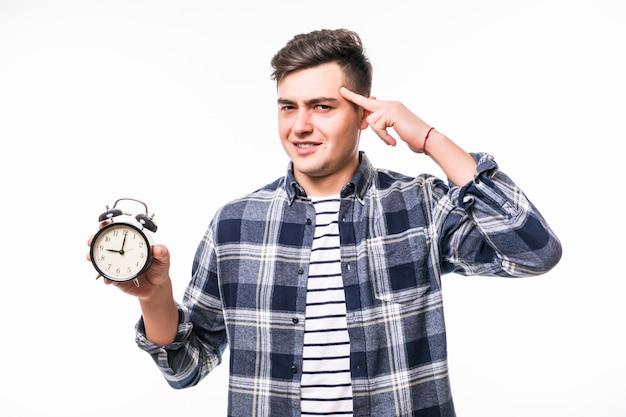 Homem estritamente aponta para o despertador isolado no estúdio na parede branca