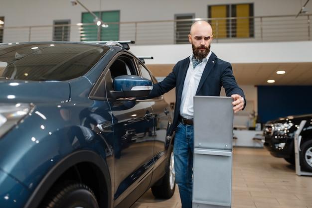 Homem estuda a configuração do transporte na concessionária. cliente em showroom de veículos novos, homem comprando automóvel, concessionária de automóveis