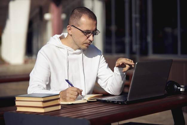 Homem estuda em laptop e escreve em um notebook sentado na rua à mesa. distanciamento social durante o coronavírus