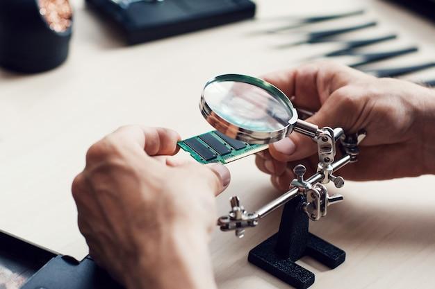 Homem estudando micro circuito em oficina