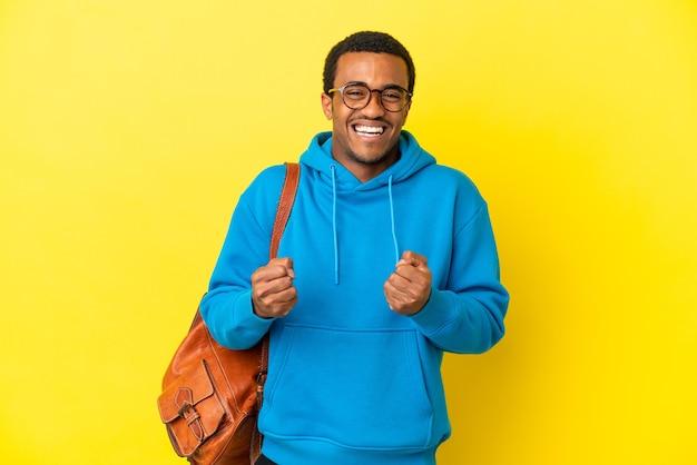 Homem estudante afro-americano sobre fundo amarelo isolado comemorando vitória na posição de vencedor